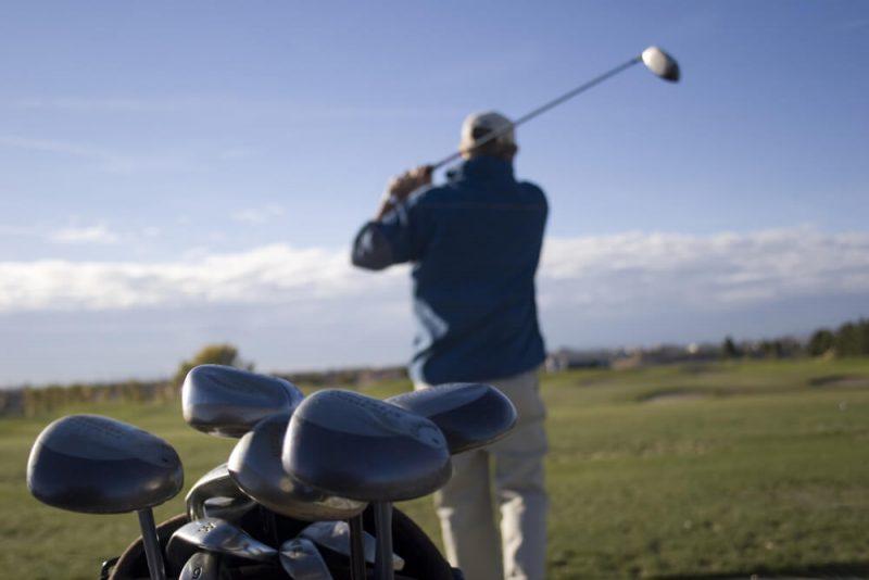 male hitting golf ball