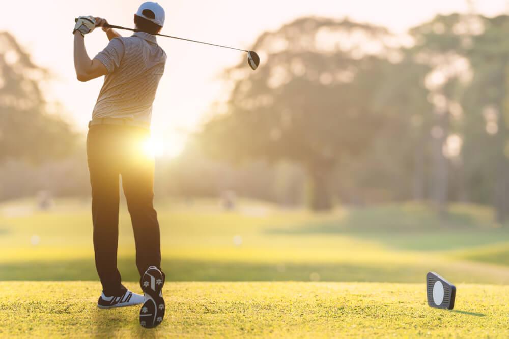 Golfer he's golfing in sunlight of the morning